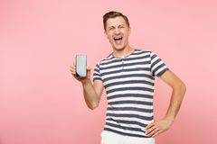 Portrait of man in striped t-shirt showing mobile phone camera with blank black empty screen copy space isolated on. Trending pastel pink background. People royalty free stock photography