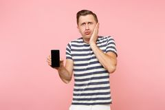 Portrait of man in striped t-shirt showing mobile phone camera with blank black empty screen copy space isolated on. Trending pastel pink background. People stock photos