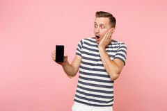 Portrait of man in striped t-shirt showing mobile phone camera with blank black empty screen copy space isolated on. Trending pastel pink background. People royalty free stock image