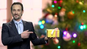 Portrait of man in suit pointing at gift box. stock video footage