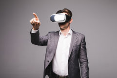 Portrait of man in a suit with virtual reality glasses on his head pointed with hand isolated on grey background. Portrait of male in a suit with virtual Stock Photos