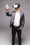 Portrait of man in a suit with virtual reality glasses on his head pointed with hand isolated on grey background. Stock Photo