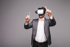 Portrait of man in a suit with virtual reality glasses on his head pointed with hand isolated on grey background. Portrait of male in a suit with virtual Royalty Free Stock Photo