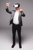 Portrait of man in a suit with virtual reality glasses on his head pointed with hand isolated on grey background. Stock Photos