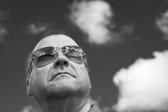 Portrait of man in sunglasses. Monochrome portrait of middle-aged man wearing sun glasses with background of cloud and sky stock photo