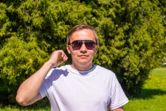 Portrait of a man in sunglasses and a white T-shirt standing outside in park royalty free stock image