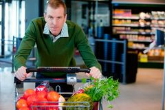 Portrait of a Man in Supermarket. Portrait of a man pushing a grocery cart in a supermarket Stock Photo