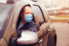 Portrait of a man with a surgical mask on his face in a car