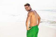 Portrait of man in swim shorts standing on beach Stock Photos