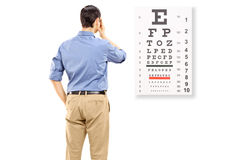 Portrait of a man taking eyesight test. Isolated on white background Royalty Free Stock Photography