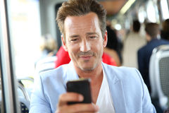 Portrait of a man taking tramway using smartphone Stock Images