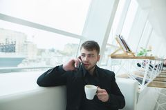 Man talking on the phone with a cup of hot drink in his hands. A man with a beard sits in coffee shop and dine. Stock Photo