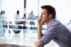 Portrait of man talking on phone, office interior Royalty Free Stock Images