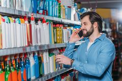 portrait of man talking on smartphone while choosing detergents royalty free stock images