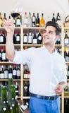 Portrait of man tasting wine sample in glass in shop Stock Image