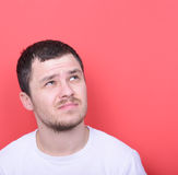 Portrait of man thinking against red background Stock Photo