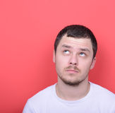 Portrait of man thinking and looking up against red background Stock Images