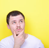 Portrait of man thinking and looking up against yellow backgroun Stock Photo