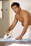Portrait of man in towel ironing clothes on a stand Stock Images