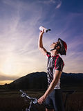 Portrait of man training on mountain bike. Sports activity: young adult cyclist on mountain bike spilling water on face from bottle. Vertical shape, side view Royalty Free Stock Photo