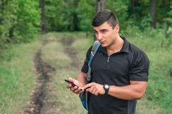 Portrait of a man traveller searching connection on the phone in the forest. Royalty Free Stock Image