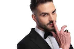 Portrait of a man in tuxedo making the silence gesture. Closeup portrait of a man in tuxedo making the silence gesture with finger over mouth on white background Stock Image