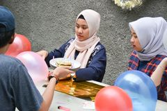 Portrait of man and two`s hijab woman preparing birthday surprise party on concrete table. Portrait of men and two`s hijab women preparing birthday surprise royalty free stock photo