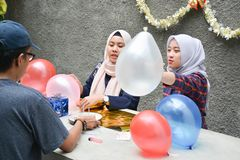 Portrait of man and two`s hijab woman preparing birthday surprise party on concrete table. Portrait of men and two`s hijab women preparing birthday surprise stock image