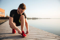 Portrait of a man tying shoelaces on sports shoe Stock Images