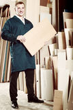 Portrait of man in uniform choosing compressed densified wood in Royalty Free Stock Photography