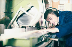 Portrait of man in uniform working on electrical rotary saw indo Stock Images