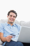 Portrait of a man using his credit card to buy online Royalty Free Stock Image