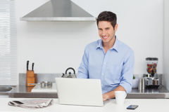Portrait of a man using a laptop in the kitchen Stock Images
