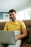 Portrait of man using laptop in living room Royalty Free Stock Photography