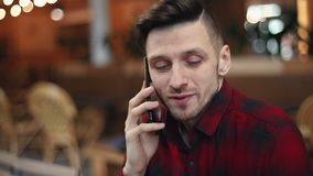 Portrait of a Man Using Smartphone. Portrait of man wearing casual plaid shirt tells something to the interlocutor on a smartphone while sitting in a cafe stock video