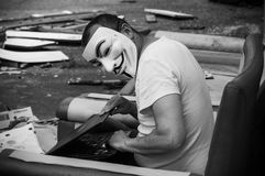 Portrait of man with Vendetta mask and coumputer in abandoned  factory  on vintage armchair Royalty Free Stock Photo