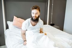 Portrait of a man waking up in the morning. Portrait of a bearded man waking up in the bed, feeling frustrated or uncomfortable in the morning royalty free stock photography