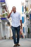 Portrait of man walking on street talking on mobile phone. Full length portrait of man walking on street talking on mobile phone Royalty Free Stock Image