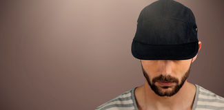 Composite image of portrait of man wearing black hat. Portrait of man wearing black hat against brown background Royalty Free Stock Photo