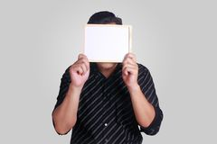 Young Asian Man Covering His Face With Small Whiteboard Royalty Free Stock Photo