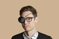 Portrait of a man wearing eye patch on glasses over colored background Royalty Free Stock Images
