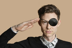 Portrait of a man wearing eye patch saluting over colored background Royalty Free Stock Images