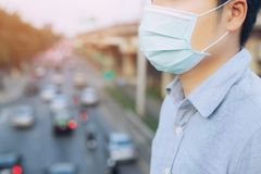 Portrait of man wearing facial hygienic mask nose outdoors. Ecology, air pollution car, Environmental and virus protection concept flu health against toxic stock photography