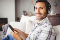 Portrait of man wearing headphones while using mobile phone Royalty Free Stock Photography