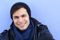 Portrait of man wearing a knitted hat, leather jacket and scarf for the cold weather Stock Image