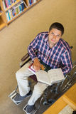 Portrait of a man in wheelchair reading a book in library Stock Photos