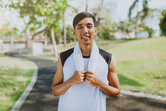 Portrait a man with white towel resting after workout sport exercises outdoors at public park , Healthy lifestyle Royalty Free Stock Photography
