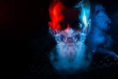 Portrait of a man who is angry and has bad emotions with mask from a smoke around on a black isolated background. The face of the royalty free stock image