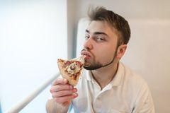 Portrait of a man who eats a piece of pizza and looks into the camera. A man with a beard enjoys the taste of hot pizza Royalty Free Stock Photography