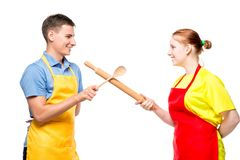portrait of a man and a woman in an apron with kitchen utensils fighting on a white stock image